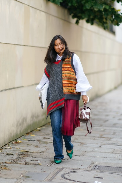 A guest wears a white oversized shirt with puff sleeves, a gray wool oversized sleeveless pullover w...