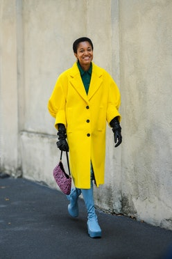 MILAN, ITALY - SEPTEMBER 24: Tamu McPherson wears gold pendant earrings, a dark green wool polo shir...