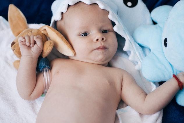 Beautiful baby boy laying in shark towel
