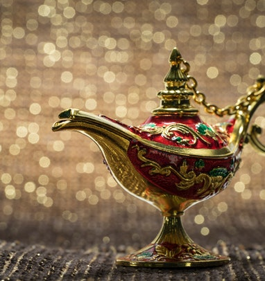 Close-Up Of Magic Lamp on fabric against golden bokeh background