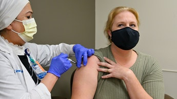 Orange, CA - August 19: Nurse Mary Ezzat administers a Pfizer COVID-19 booster shot to Jessica M. at...