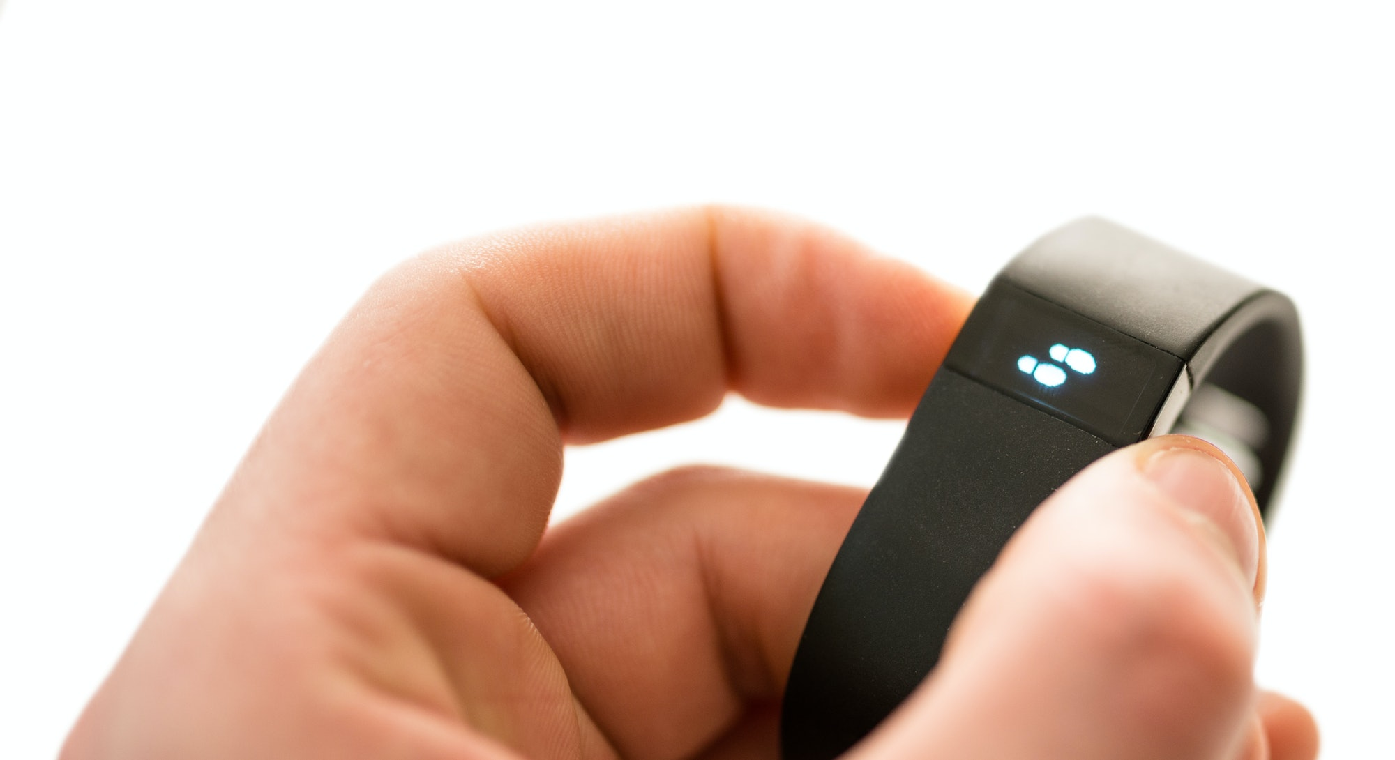 Florence, Italy - March 7, 2014: Close up of the new Fitbit Force on the hand of a guy showing shows...