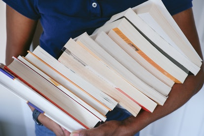 Close-up of unrecognizable black woman carrying a heap of books
