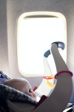 A baby boy sits in a car seat during an airplane flight. (Photo by James Leynse/Corbis via Getty Ima...