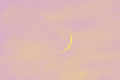 Crescent moon adorned by red clouds during a sunset. A beautiful capture that can be used as a backg...