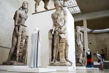 A woman looks at dresses displayed among large plaster casts by French sculptor Antoine Bourdelle (1...