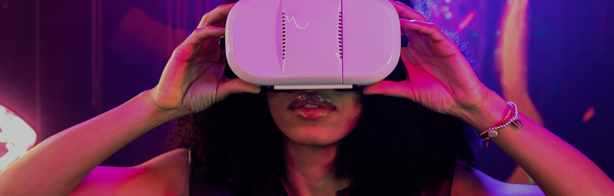 Young adult Afro American woman using Virtual Reality headset with both hands holding it at night wi...