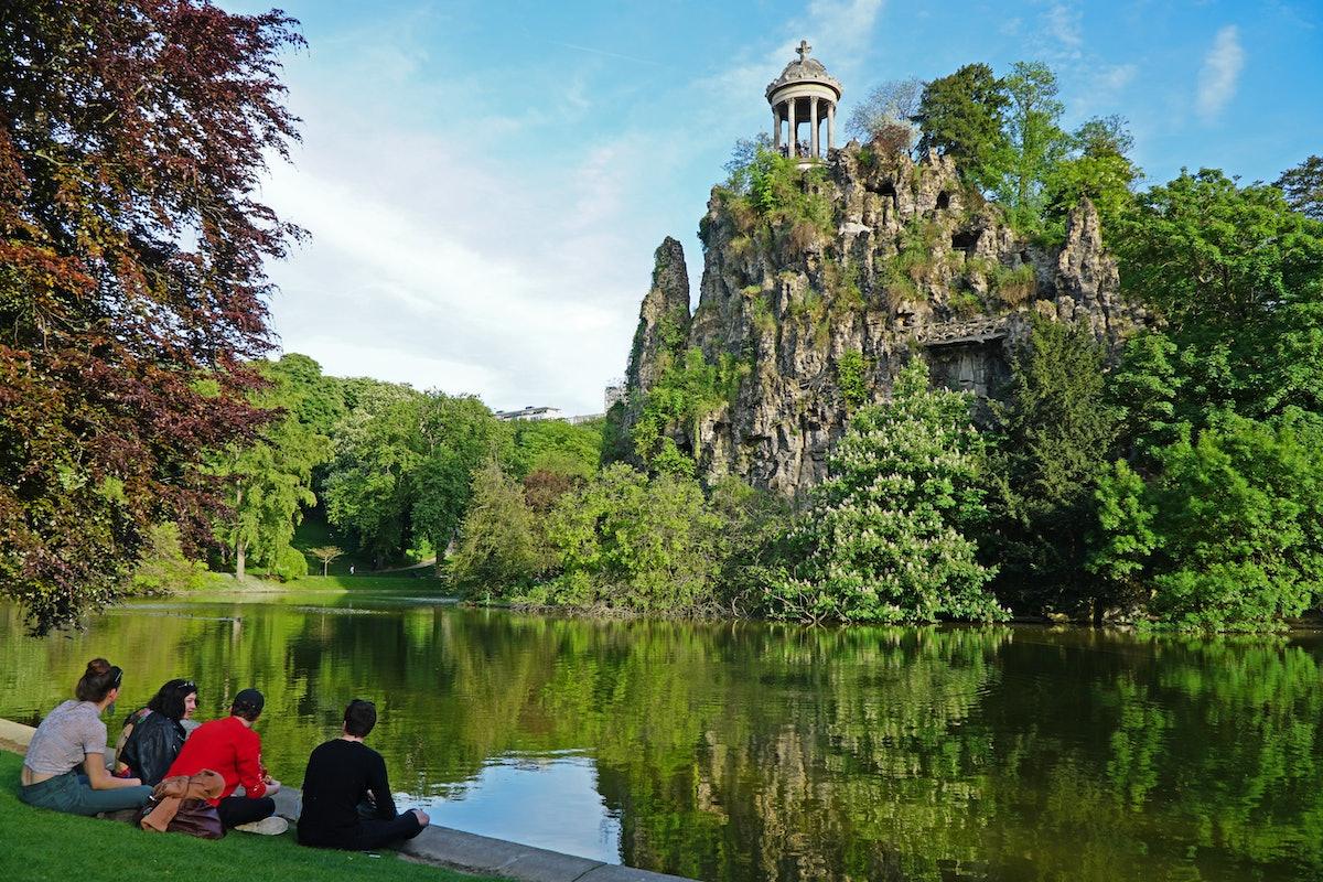 گروهی از جوانان نشسته در لبه دریاچه Buttes Chaumont در بهار ، 24 آوریل 2017 ، پاریس 19 ...