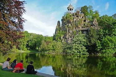 Groupe de jeunes gens assis au bord du lac des Buttes Chaumont au printemps, 24 avril 2017, Paris 19...