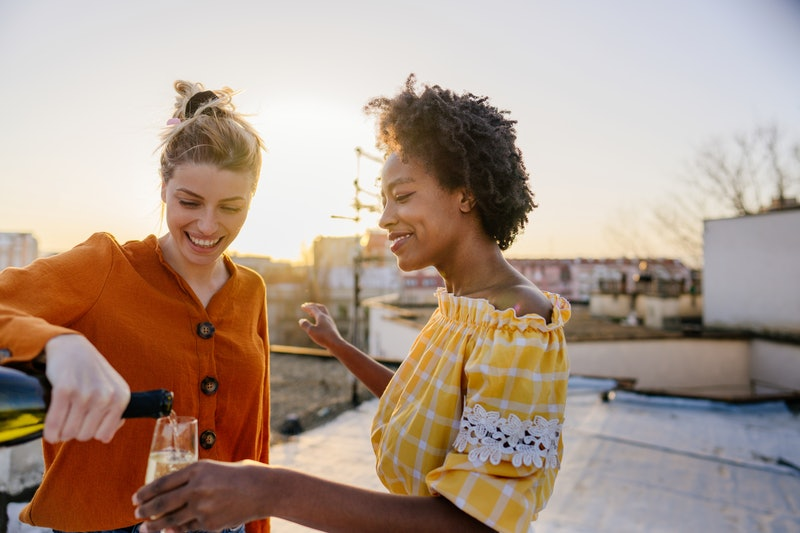 Smiling young women pour a glass of champagne. These are the traits of libra-scorpio cusp signs.