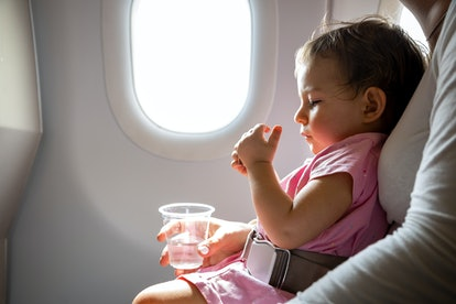 baby sitting on parent's lap on airplane