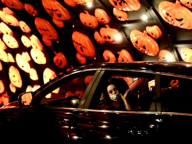 A girl wearing a face mask takes part in a drive-thru Halloween experience while in her car. (Photo ...
