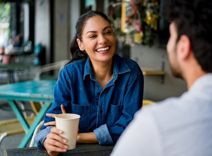 Happy Latin American woman on a date at a cafe talking to a man while drinking coffee and laughing -...