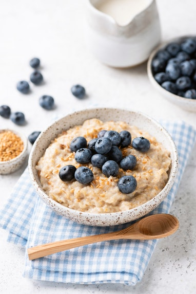 Oatmeal bowl with blueberries and flax seeds on blue textile. Healthy breakfast meal