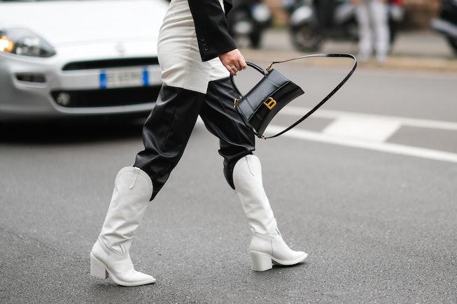 MILAN, ITALY - SEPTEMBER 25: A guest wears a black cropped blazer jacket, half white denim an half b...