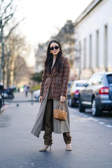 PARIS, FRANCE - JANUARY 20: Tamara Kalinic wears sunglasses, earrings, a beige turtleneck, a colorfu...