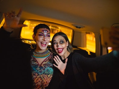Two girls are taking a selfie in a car during a drive-thru Halloween experience.