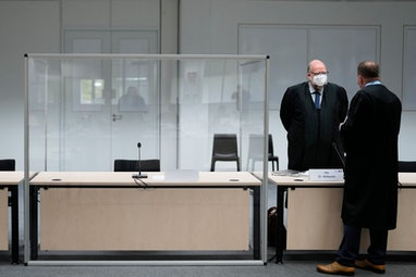 Two lawmakers stand next to an empty seat of the defendant at the courtroom, prior to a trial agains...