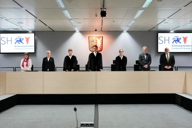 Presiding judge Dominik Gross (C) and the judges pose for the media after arriving for a trial again...