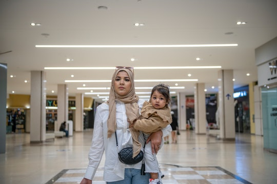 A young Muslim mother walks through an airport with her infant daughter in her arms on her hip.  The...