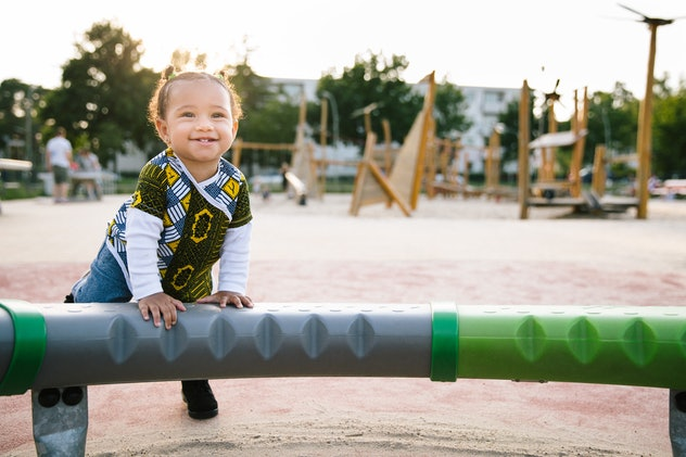 Carefree toddler playing on a playground in summer