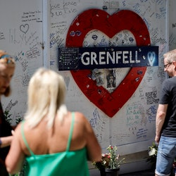 People look at a memorial to the victims of the Grenfell Tower fire, in west London on June 14, 2021...