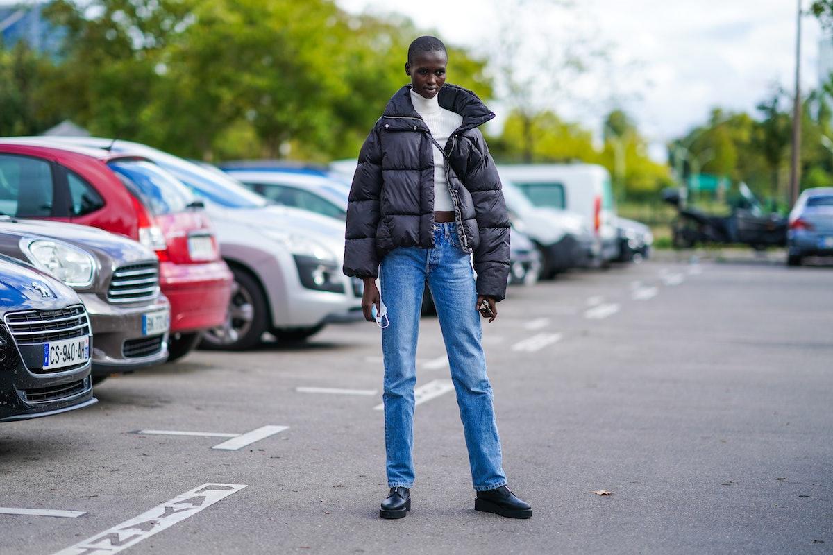 PARIS, FRANCE - OCTOBER 03: A model wears a black winter oversized puffer jacket, a white wool turtl...