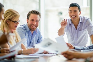 A multi-ethnic group of business professionals are working together in the boardroom.