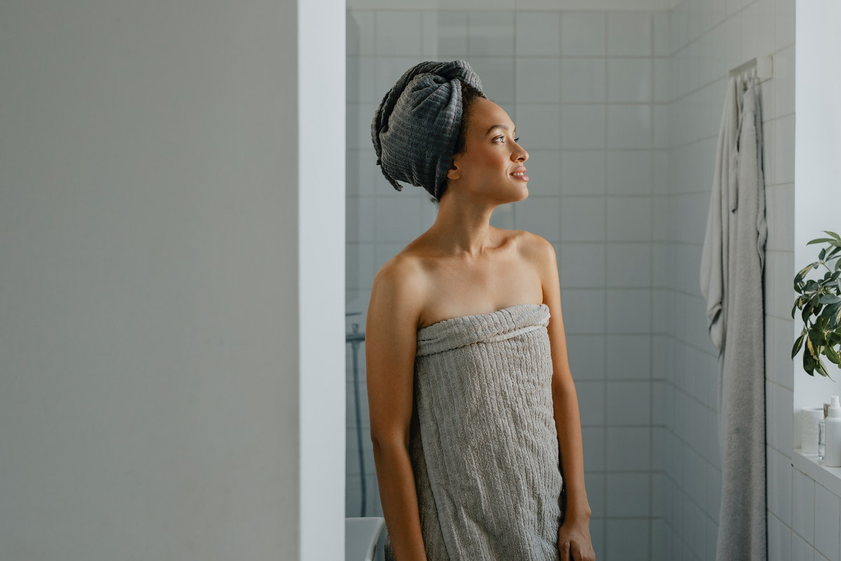 A young Black woman gets ready after a daily shower