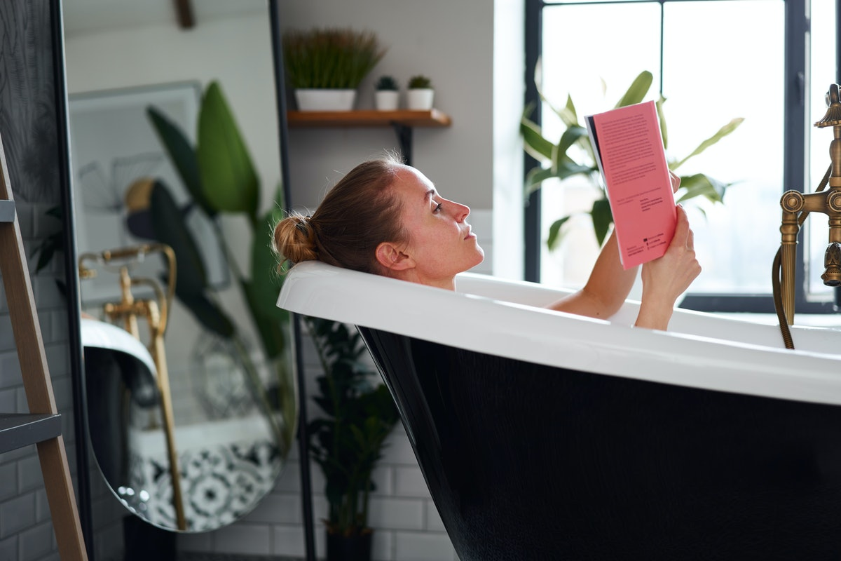 young woman reading a book while taking bath