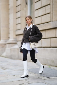 Xenia Adonts wears silver earrings, a pearls necklace, a white long oversized shirt from Attire The ...