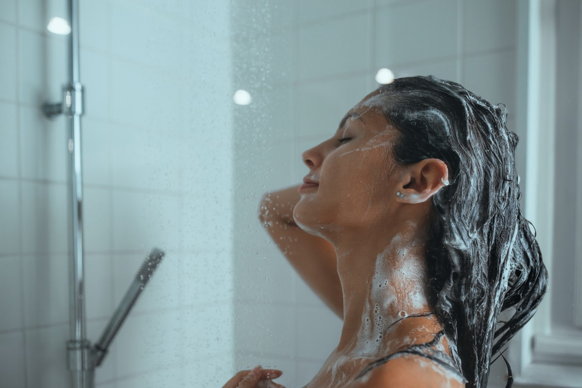 A young woman lathers her hair with shampoo as she takes a daily shower