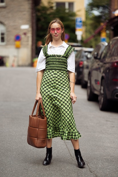 STOCKHOLM, SWEDEN - SEPTEMBER 02: Guest wearing white shirt with checked light green dress and brown...