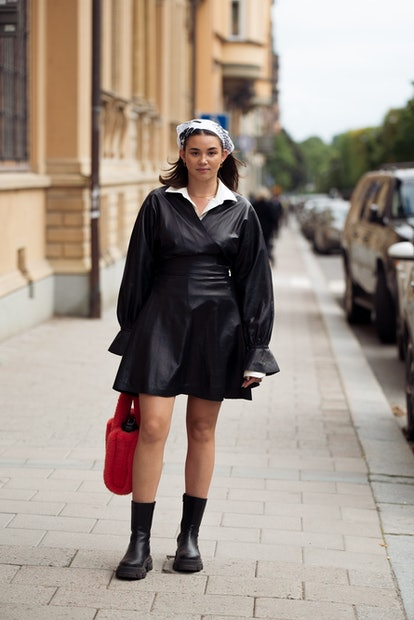 STOCKHOLM, SWEDEN - SEPTEMBER 01: Guest wearing black leather dress and wearing head accessory balck...