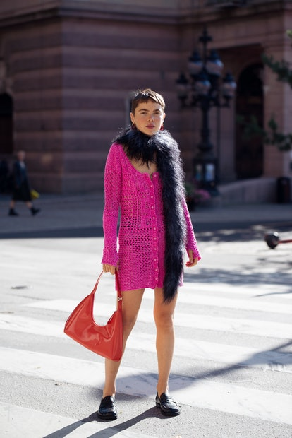 STOCKHOLM, SWEDEN - AUGUST 31: Emma Fridsell wearing pink knitted dress, red bag, red earrings and f...