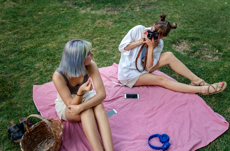 Two women take photos of each other on a picnic blanket, drifting apart as friends.
