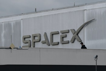 A pedestrian wears a face mask while crossing a bridge from the Space Exploration Technologies Corp....