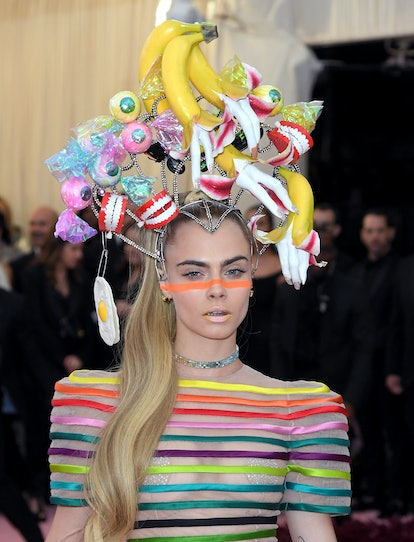 Cara Delevingne keeps her makeup pared down at the 2019 Met Gala — except for a neon stripe across h...