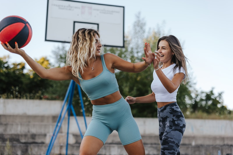 Sporty female friends playing basketball 'one on one' outdoors. Here are signs your friends are jeal...