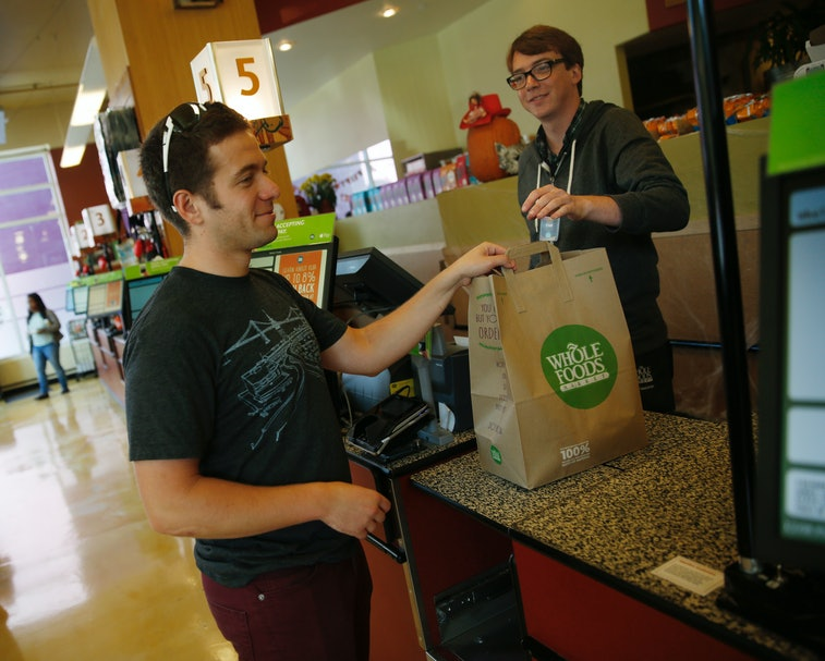 Leo Romanovsky (l to r), of San Francisco collects his purchases from Ethan Bridges, cashier,  after...