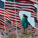 A girls stands amongst US national flags erected by students and staff from Pepperdine University to...