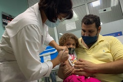 TOPSHOT - Pedro Montano holds his daughter Roxana Montano, 3, while she is being vaccinated against ...