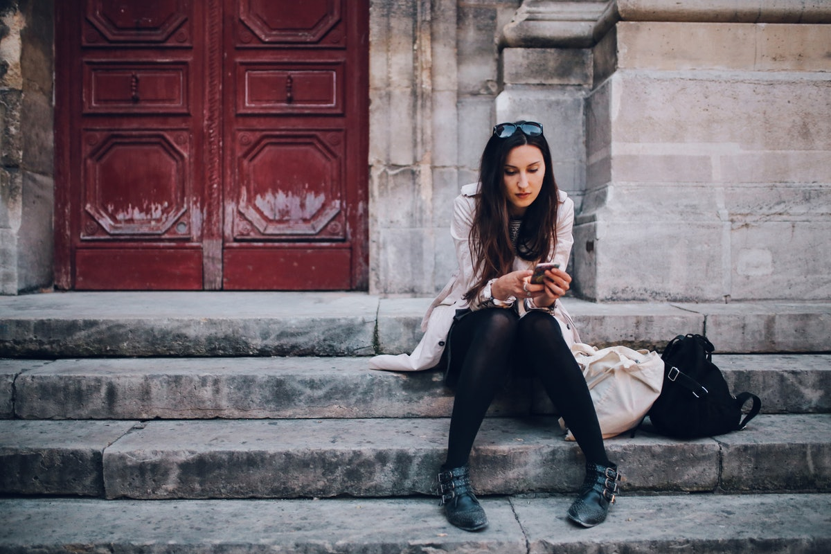 Vintage toned image of a young Parisian woman checking cellphone while sitting on the stairs in the ...