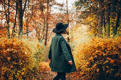 Girl in hat standing back at autumn forest in October 2021, the worst month for her zodiac sign.