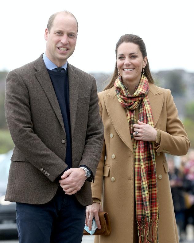 Kate Middleton puts on a long coat.