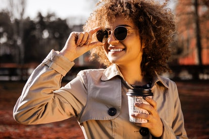 Beautiful young woman smiling wearing sunglasses and drinking a takeaway cup of coffee outside