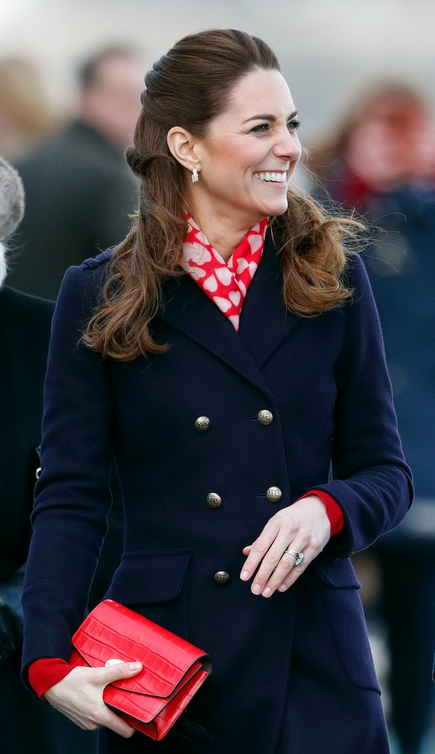 Kate Middleton wears a navy blue coat and a red scarf.