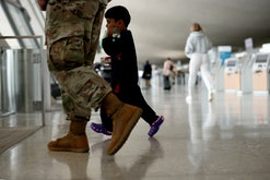 DULLES, VIRGINIA - AUGUST 31: An Afghan boy walks with a U.S. service member as he and his family ar...