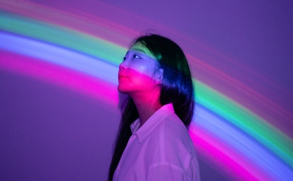 young woman lit by rainbow-colored lights as she looks to the left, reflecting on how october 15, 20...