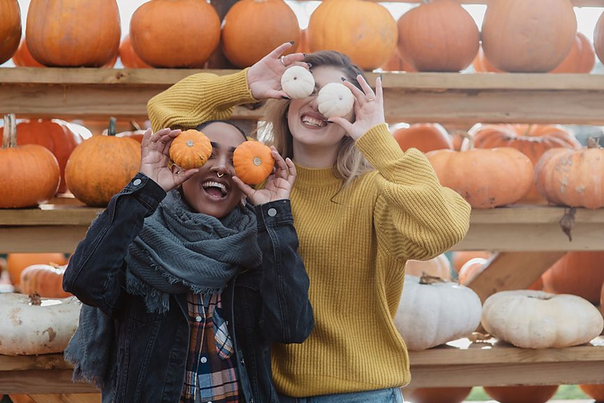 Pumpkin puns for Instagram are great for these two friends holding mini pumpkins over there eyes in front of a wall of pumpkins.